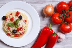 Spaghetti with tomatoes, olives and basil  and ingredients on th Stock Photography