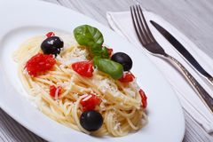 Spaghetti with tomatoes, olives, basil and parmesan cheese Royalty Free Stock Photos