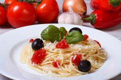 Spaghetti with tomatoes, olives and basil on the table Royalty Free Stock Photos