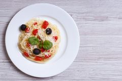 Spaghetti with tomatoes, olives and basil on the table Royalty Free Stock Photo