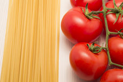 Spaghetti and tomatoes on a table ready to cook Stock Images