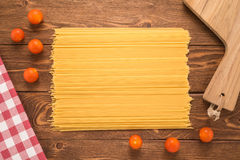 Spaghetti with tomatoes, tablecloth and cutting board Royalty Free Stock Images