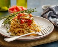Spaghetti with tomatoes and thyme in a plate on a blue table royalty free stock photo