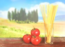 Spaghetti and tomatoes with tuscian landscape Royalty Free Stock Photo
