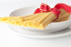 Spaghetti - traditional Italian cuisine. Uncooked spaghetti in dish on white background royalty free stock image