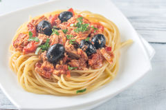 Spaghetti with tuna and black olives. Portion of spaghetti with tuna and black olives on the wooden table stock photography