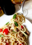 Spaghetti with tuna fish and basil in a fork. Spaghetti in a fork with tuna, basil and tomatoes, glass of white wine and wine bottle in the background Royalty Free Stock Images