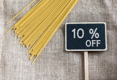 Spaghetti uncooked and sale 10 percent off drawing on blackboard. And gunny background Royalty Free Stock Image