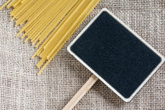 Spaghetti uncooked and small blackboard Royalty Free Stock Images