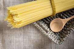 Spaghetti uncooked and spoon wood in basket Stock Image
