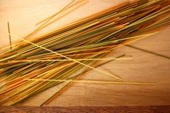 Spaghetti variopinti su fondo di legno Fotografie Stock Libere da Diritti