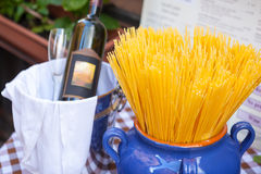 Spaghetti in vase and bottle of red wine. Stock Photography