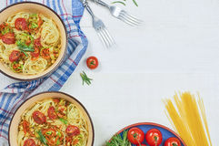 Spaghetti with vegetables on a plate. Serving on a white wooden table. An Italian-American dish. Horizontal top view, rustic style. Selective focus Royalty Free Stock Images