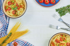 Spaghetti with vegetables on a plate. Serving on a white wooden table. An Italian-American dish. Horizontal top view, rustic style. Selective focus Royalty Free Stock Photography