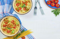 Spaghetti. With vegetables on a plate. Serving on a white wooden table. An Italian-American dish. Horizontal top view, rustic style. Selective focus Royalty Free Stock Images