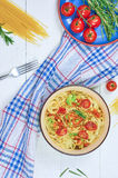 Spaghetti with vegetables on a plate. Serving on a white wooden table. An Italian-American dish. Vertical top view, rustic style. Selective focus Royalty Free Stock Photography