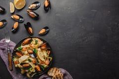 Spaghetti vongole, Włoski owoce morza makaron z milczkami i mussels, w talerzu z ziele i szkłem biały wino na wieśniaka kamieniu fotografia royalty free