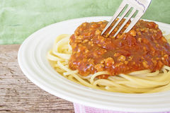 The spaghetti in white plate with a fork on a lap. Royalty Free Stock Photos
