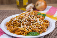 Spaghetti on white plate. Spaghetti with grated parmesan cheese and basil leaves.  Onion, mushroom, uncooked pasta and oil in the background Royalty Free Stock Photography