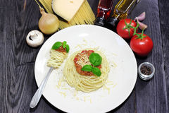Spaghetti on white plate with pasta and tomatoes Stock Images
