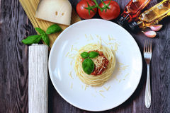 Spaghetti on white plate with pasta and tomatoes Stock Photo