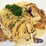 Spaghetti white sauce. Pasta with white mushrooms sauce and fried pork Stock Photos