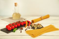 Spaghetti on a white wooden background with tomatoes and various spices royalty free stock images