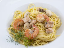 Spaghetti wiht shrimps. Spaghetti with shrimps and salmon decorated with some dill Royalty Free Stock Photos