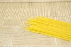 Spaghetti  on a wooden surface. Dried pasta, spaghetti,  scattered on a wooden base Stock Photography