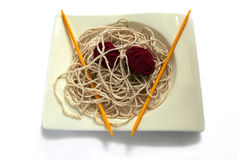 Spaghetti Wool. Fun Concept with Spaghetti and meat balls created out of balls of wool with kniting needles Royalty Free Stock Photo
