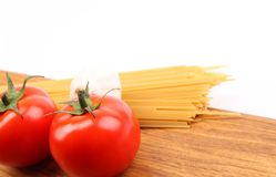 Spaghetti, yomato, garlic on wooden cutting board Stock Photos