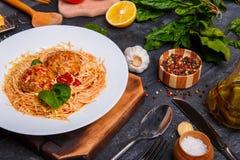Spaghetti z kraciastym serem i klopsikami na talerzu, czosnek kłama, pieprz kropi z grochami i solą, rozwidlenie zdjęcie stock