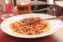 Spaghetti z kumberlandu balonze na talerzu na tle kubek piwo fotografia royalty free