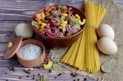 spaghetti, zout in een doos met een deksel, peper en drie eieren die in het centrum van een donkere lijst liggen stock foto's