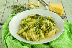 Spaghetti with zucchini and peas. Seasoned with rosemary, garlic and parmesan cheese Stock Photo