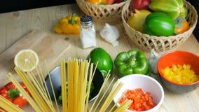 Spaghettideegwaren in glaskruik en ingrediënt op houten lijst stock videobeelden