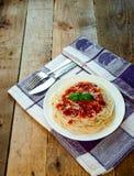 Spaghettideegwaren met Tomatensaus, Kaas en Basilicum op Houten Lijst Traditioneel Italiaans voedsel stock afbeelding