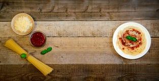Spaghettideegwaren met Tomatensaus, Kaas en Basilicum op Houten Lijst Traditioneel Italiaans voedsel royalty-vrije stock foto