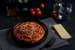 Spaghettideegwaren met tomatensaus, verse tomaat en kaas op donkere achtergrond Stock Afbeeldingen