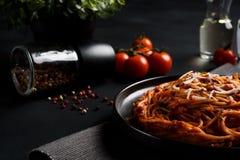 Spaghettideegwaren met tomatensaus, verse tomaat en kaas op donkere achtergrond Stock Afbeelding