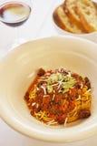 Spaghettini bolognese e un bicchiere di vino e un pane Immagini Stock