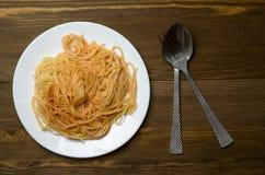 Spaghettis auf einer Platte auf einem hölzernen Hintergrund Stockbilder