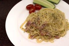 Spaghettis auf einer weißen Platte mit frischen Tomaten und Gurken lizenzfreie stockfotografie