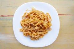 Spaghettis carbonara in der weißen Platte auf gelber Zementtabelle lizenzfreies stockfoto