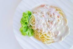 Spaghettis carbonara oder weiße Sahnesauce mit Speckumhüllung auf weißer Platte stockbild