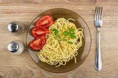 Spaghettis in der Platte mit Tomaten, Petersilie, Salz, Pfeffer und Gabel Lizenzfreies Stockbild