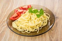 Spaghettis in der Platte mit Tomaten, Petersilie und Gabel auf Tabelle Stockfoto