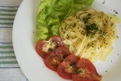 Spaghettis für Abendessen mit Tomaten und Salat Lizenzfreie Stockfotografie
