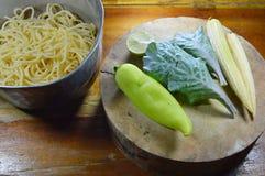 Spaghettis im Eisentopf und -gemüse auf Kreishiebblock Lizenzfreie Stockfotografie