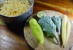 Spaghettis im Eisentopf und -gemüse auf Kreishiebblock Lizenzfreie Stockfotos